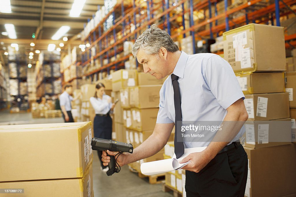 Businessman scanning shipping box in warehouse : Stock Photo