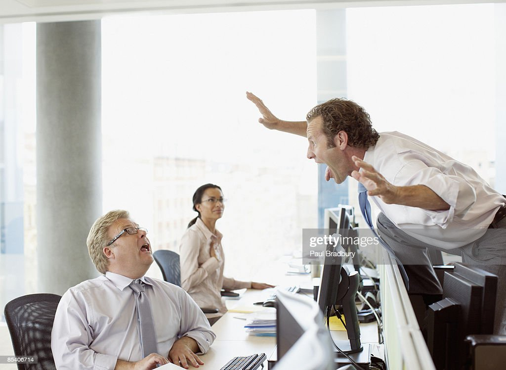 Businessman scaring co-worker in office : Stock Photo