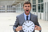 Businessman screaming while holding a big clock.