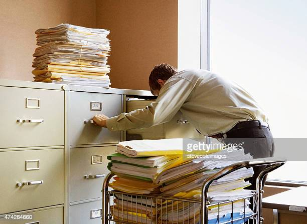 Geschäftsmann Suche nach Dokumenten in Metall-Datei Schränke.
