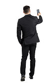 Businessman in suit searching for good phone signal rear view or taking photo. Full body length portrait isolated over white studio background
