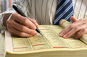 Businessman searching for something in yellow pages through indexes