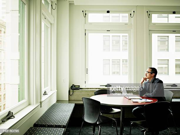Businessman seated at conference table looking out