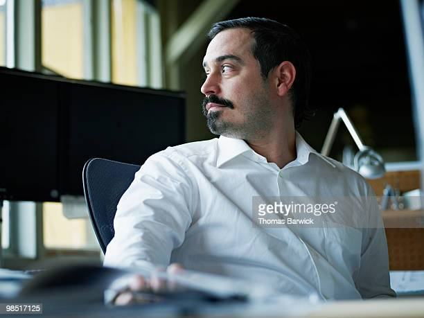 Businessman seated at desk in office looking out