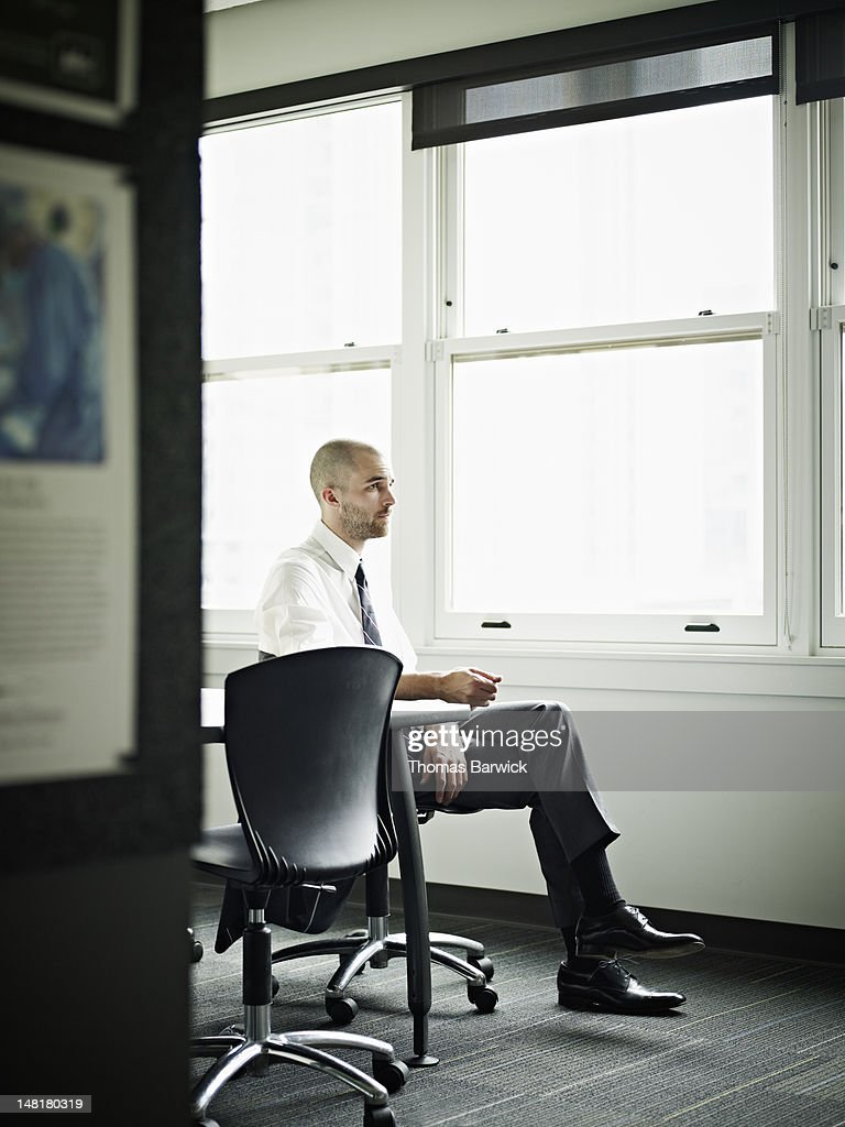 Businessman seated at office conference table : Stock Photo