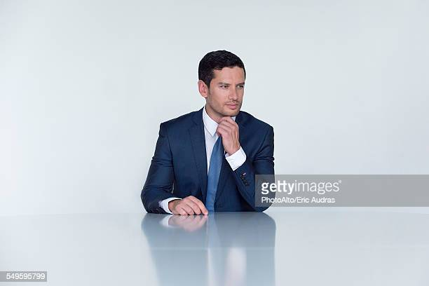Businessman seated at table, looking away in thought