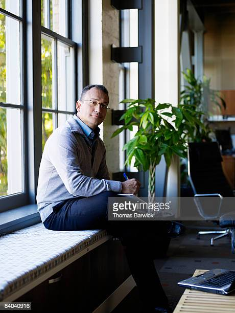 Businessman seated by office window