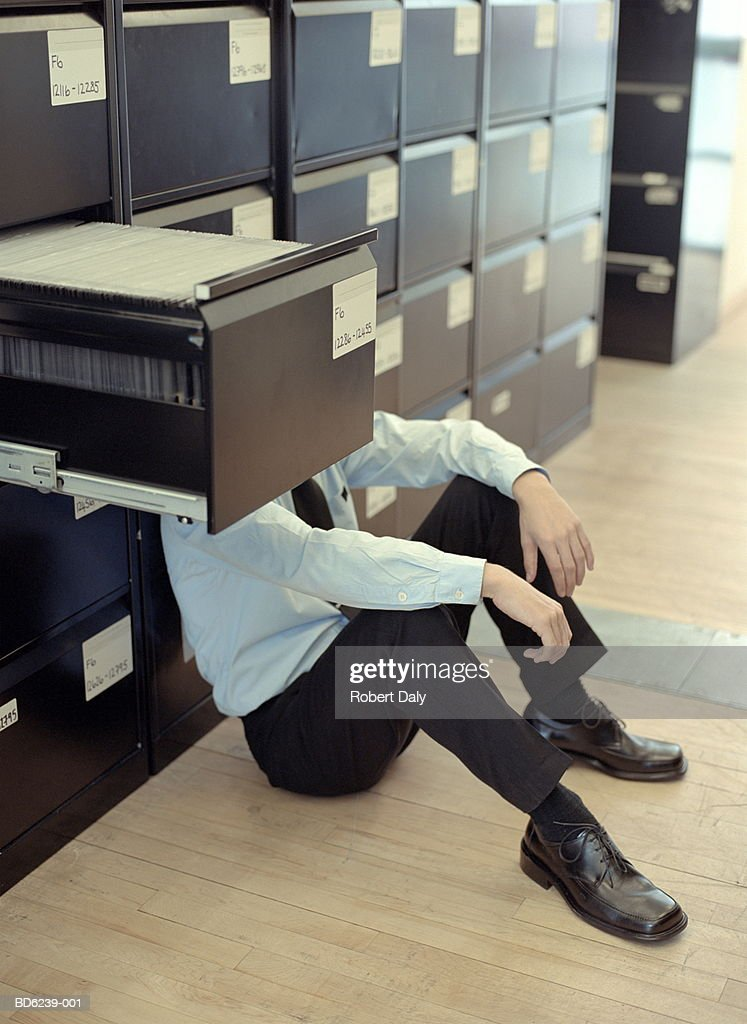 Businessman seated on floor, head behind filing cabinet drawer : Stock Photo