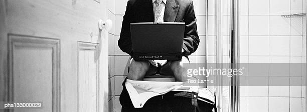 Businessman seated on the toilet, with a laptop computer, B&W