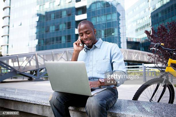 Businessman seated outside with computer and on phone