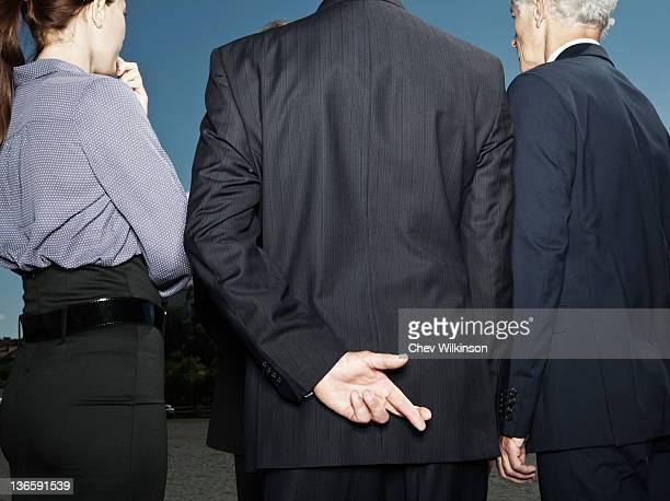 Businessman secretly crossing fingers