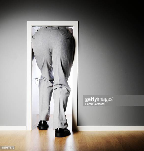 Businessman seen from behind walking through a very small door.