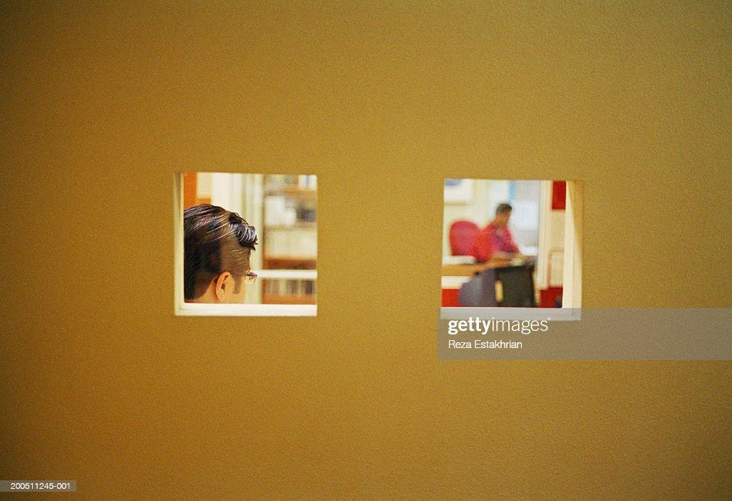 Businessman seen through window in office : Stock Photo