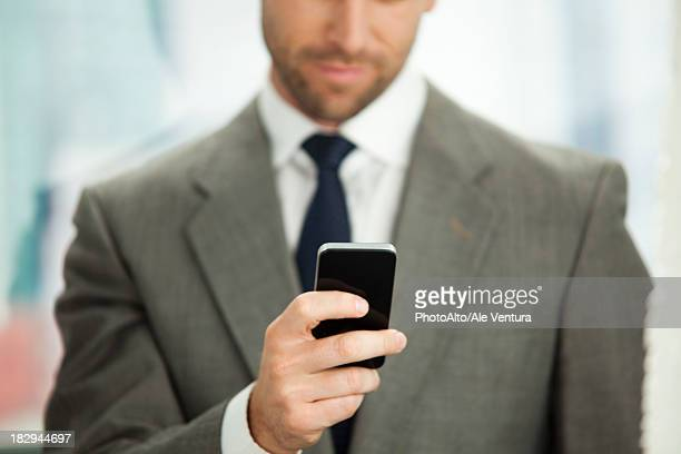 Businessman sending text message on cell phone, cropped