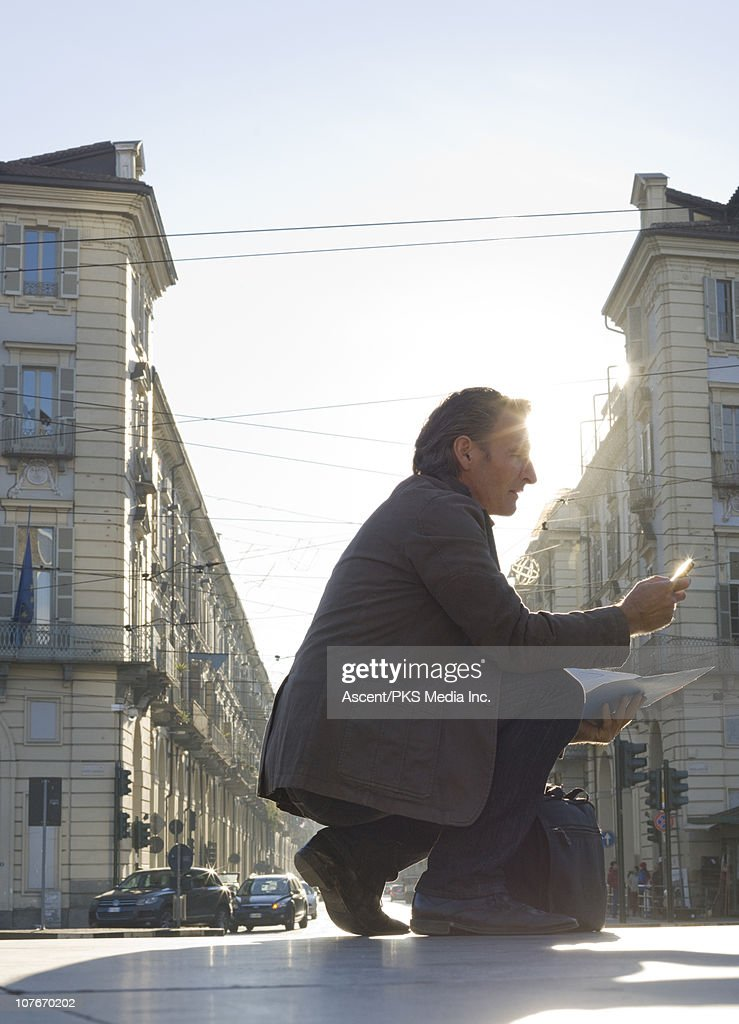 Businessman sends text at edge of city street : Stock Photo