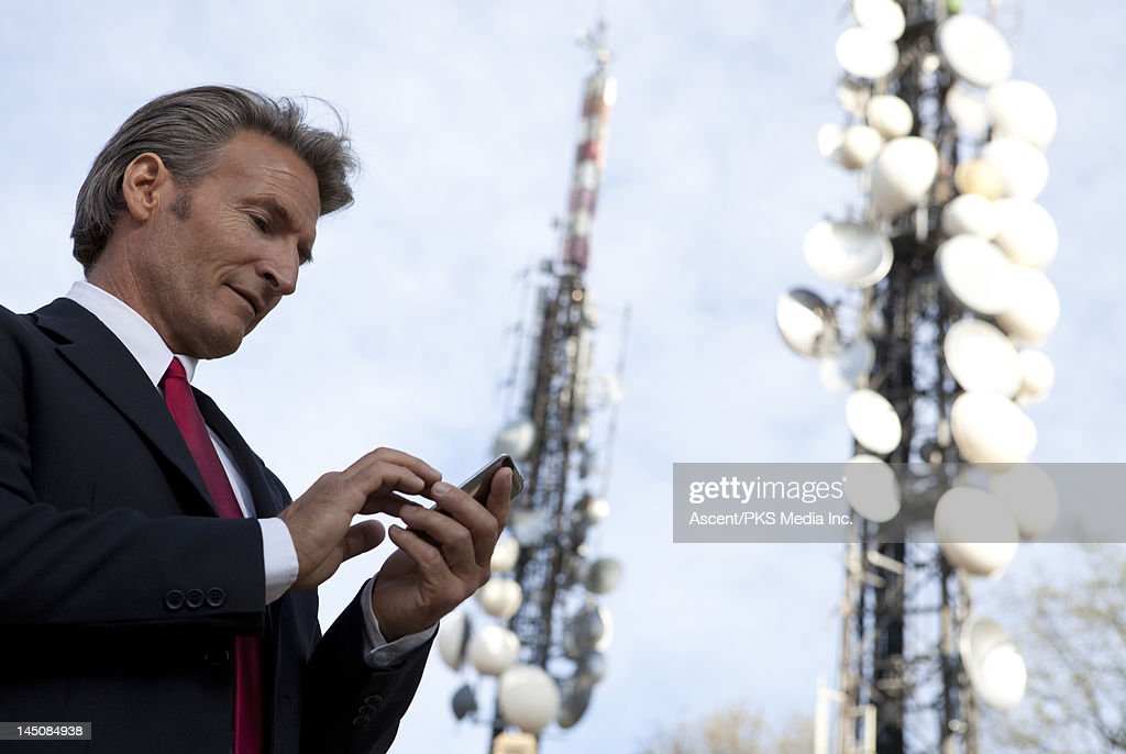Businessman sends text, communication towers : Stock Photo