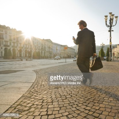 Businessman sends text while crossing piazza : Stock Photo