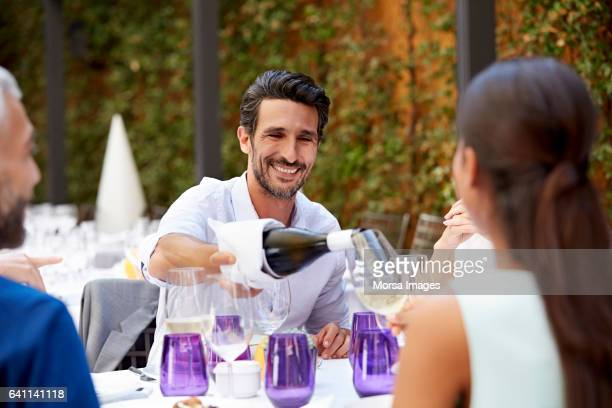 Businessman serving wine to colleague at table