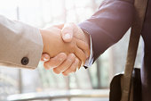 Businessman shakes hand of businesswoman, close up