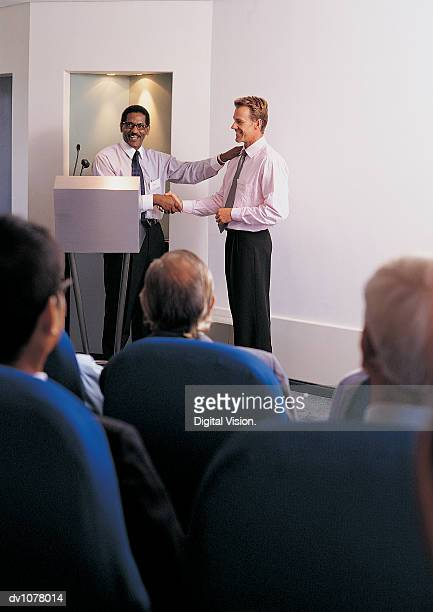 Businessman Shaking Another Businessman's Hand on a Podium During a Presentation in Front of an Applauding Audience