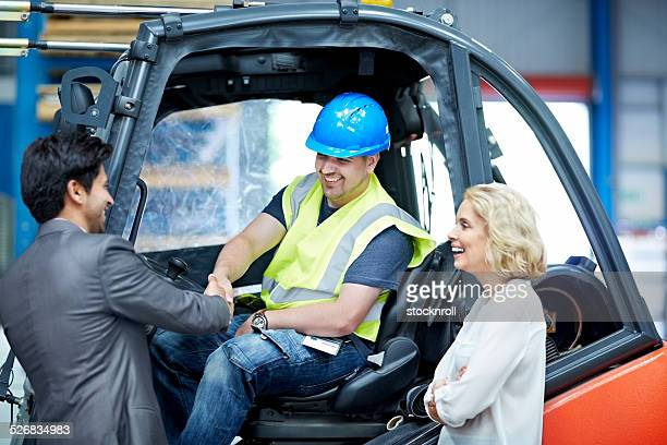Businessman shaking hand with forklift driver