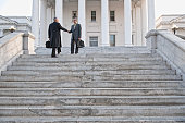 Businessman shaking hands on steps