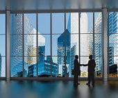 businessman shaking hands inside a business tower