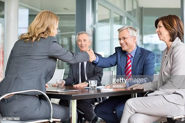 Empresario agitando las manos con un colega en reunión