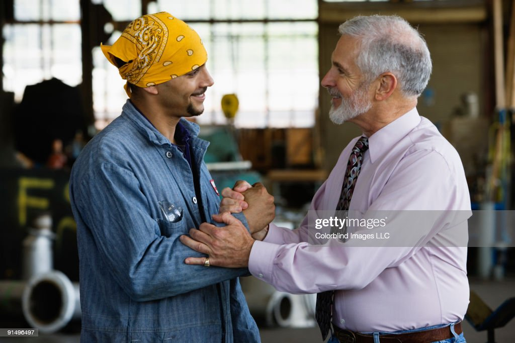 Businessman shaking hands with male warehouse worker : Stock Photo