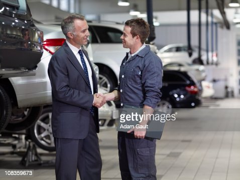 Businessman shaking hands with mechanic in auto repair shop : Stock Photo