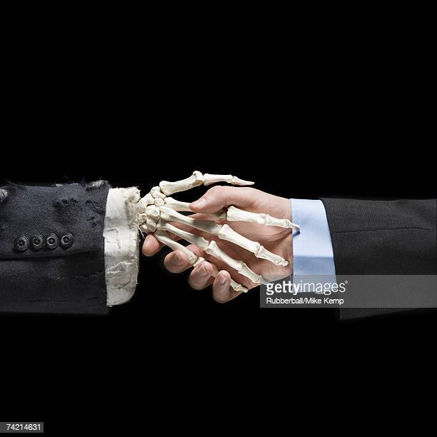 Businessman shaking hands with skeleton