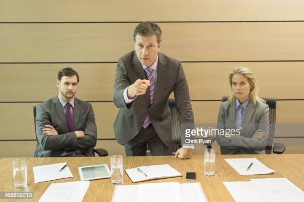 Empresário agitando o dedo em reunião