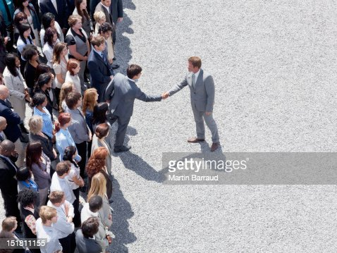 Businessman shaking mans hand in crowd : Stock Photo