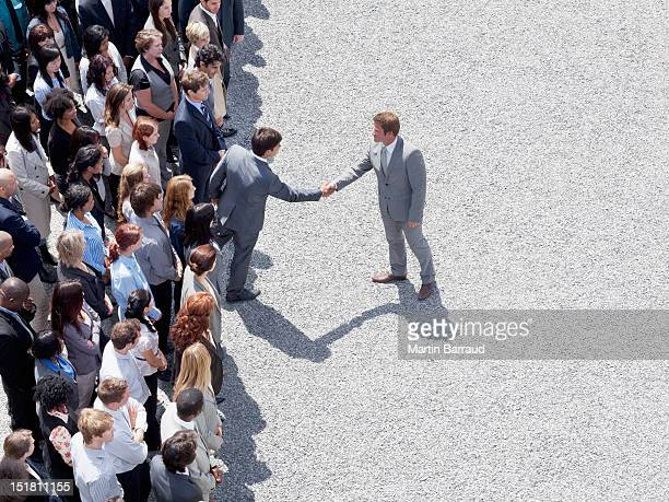 Businessman shaking mans hand in crowd