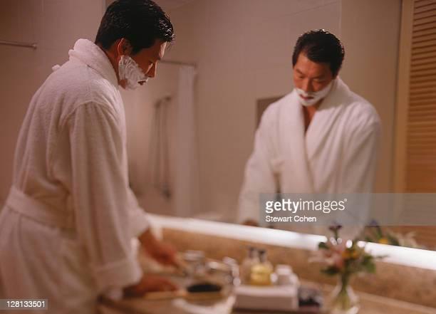 Businessman shaving in hotel