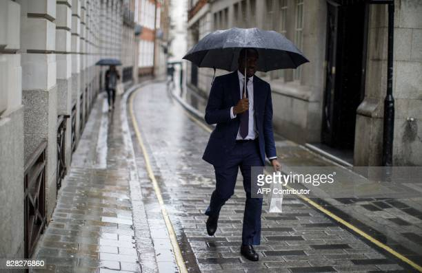A businessman shelters from the rain beneath an umbrella as he walks in the Bank of Central London on August 9 2017 World stock markets and the...