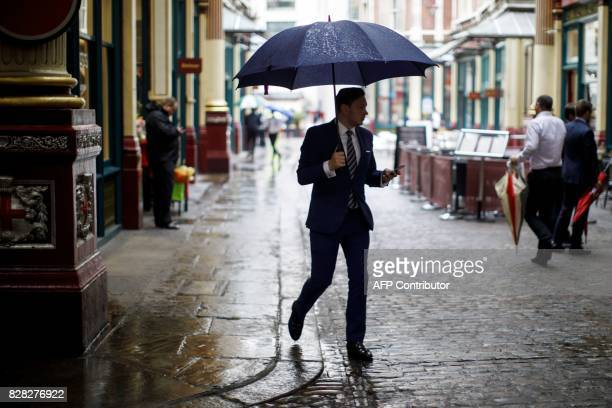 A businessman shelters from the rain beneath an umbrella as he walks in Leadenhall Market in London on August 9 2017 World stock markets and the...