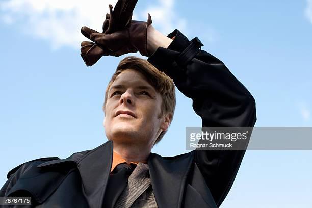 A businessman shielding his eyes