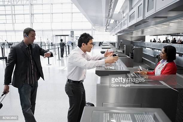 Businessman shouting at an airline check-in attendant