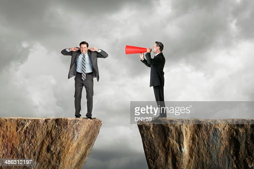 Businessman shouting at another businessman through a megaphone