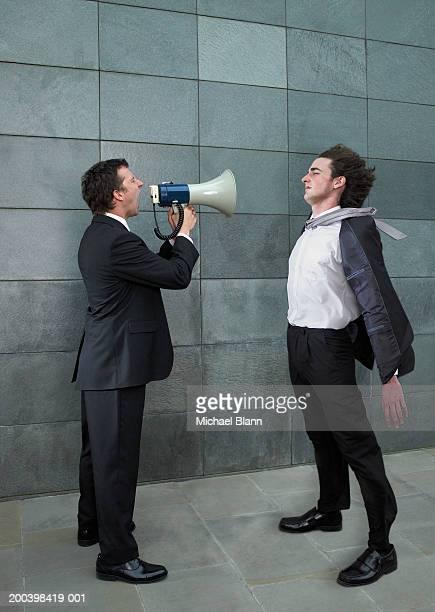 Businessman shouting at yonger colleague through megaphone, side view