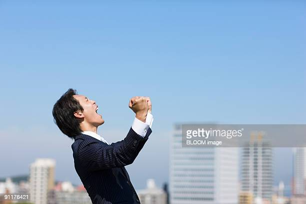 Businessman shouting, clenching fists, side view