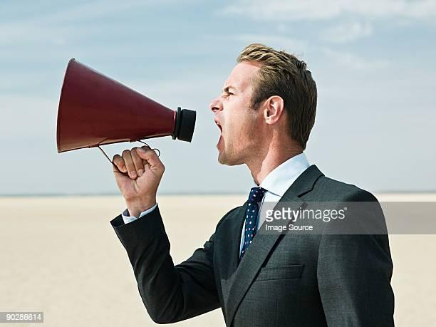 Businessman shouting in the desert