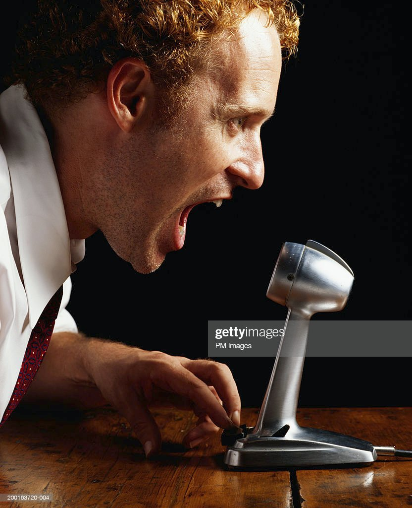 Businessman shouting into microphone, profile, close-up