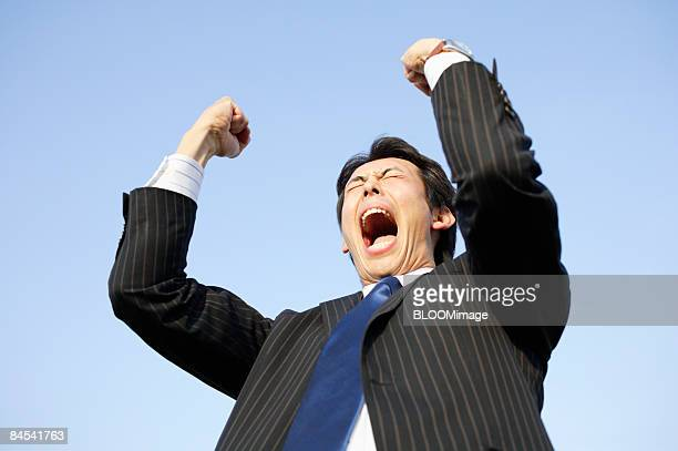 Businessman shouting, raising fists, against blue sky