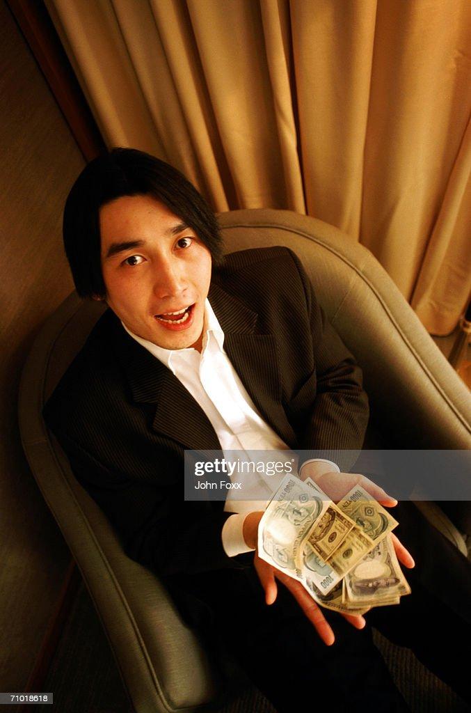 Businessman showing banknotes, portrait : Stock Photo