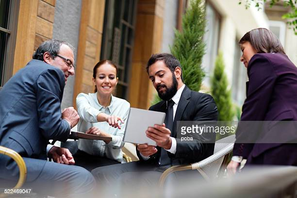 businessman showing his co-workers something on a digital tablet