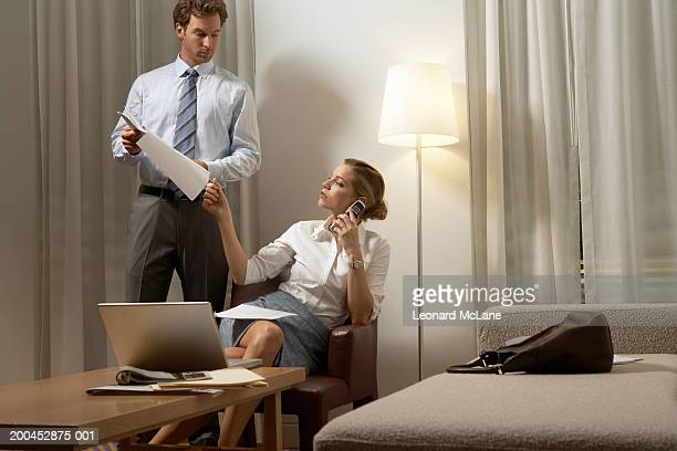 Businessman showing paperwork to businesswoman using phone in room
