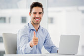 Businessman showing thumbs up while using laptop in office