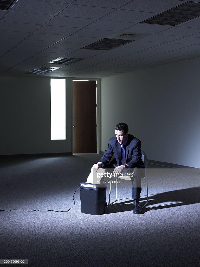 Businessman shredding papers in darkened empty room : Stock Photo